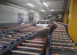 Dono de carro cercado por carrinhos de supermercado. Foto: Reprodução de Internet